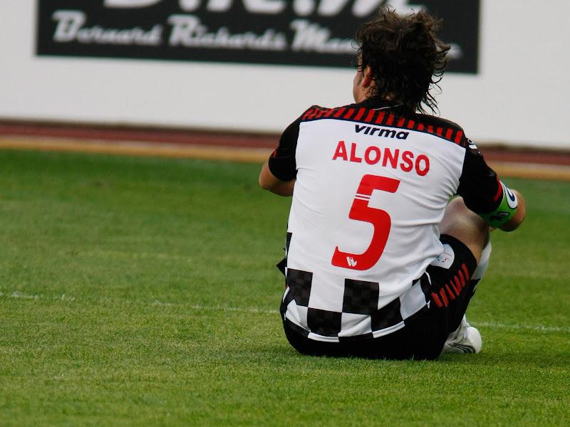 Фернандо Алонсо сидит на футбольном поле на благотворительном футбольном матче в Монте-Карло 2011