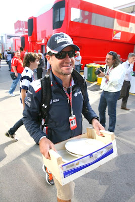 Рубенс Баррикелло несет ящик с тарелками по паддоку на Гран-при Испании 2011