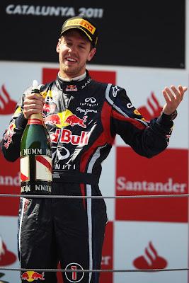 Себастьян Феттель на подиуме с бутылкой шампанского на Гран-при Испании 2011