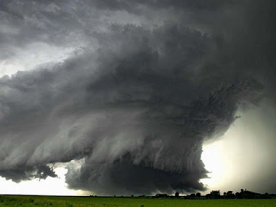 tornado brewing over a green field