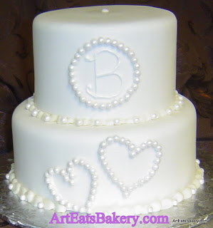 Two tier white fondant anniversary cake with unique custom sugar pearl hearts and monogram design