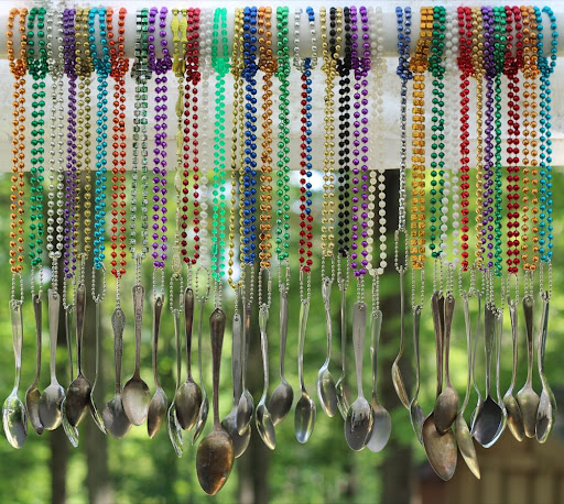 spoons attached to mardi gras necklaces, dangling like wind chimes