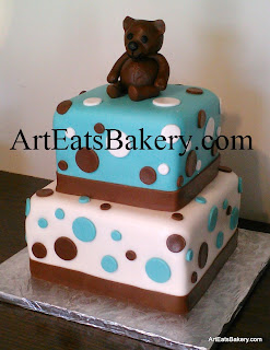 Two tier square blue, white and brown fondant modern custom creative boy's baby shower cake design with edible teddy bear topper