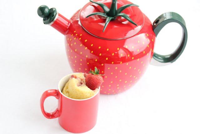 overhead photo of strawberry shaped teapot and a strawberry mug cake