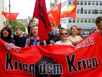 Jugendliche mit Fahnen und Transparent: »1945-2015 Krieg dem Krieg«.