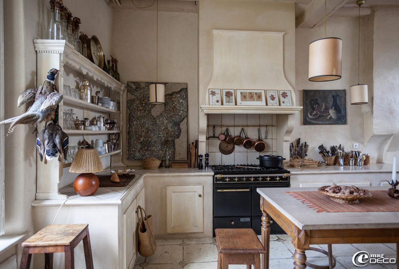 Dans la cuisine, tabourets en bois et collection de casseroles en cuivre, l'ensemble chiné à l'Isle-sur-la-Sorgue. Cuisinière 'Ambassador'