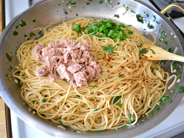 drained can of tuna added to noodles and other ingredients in skillet