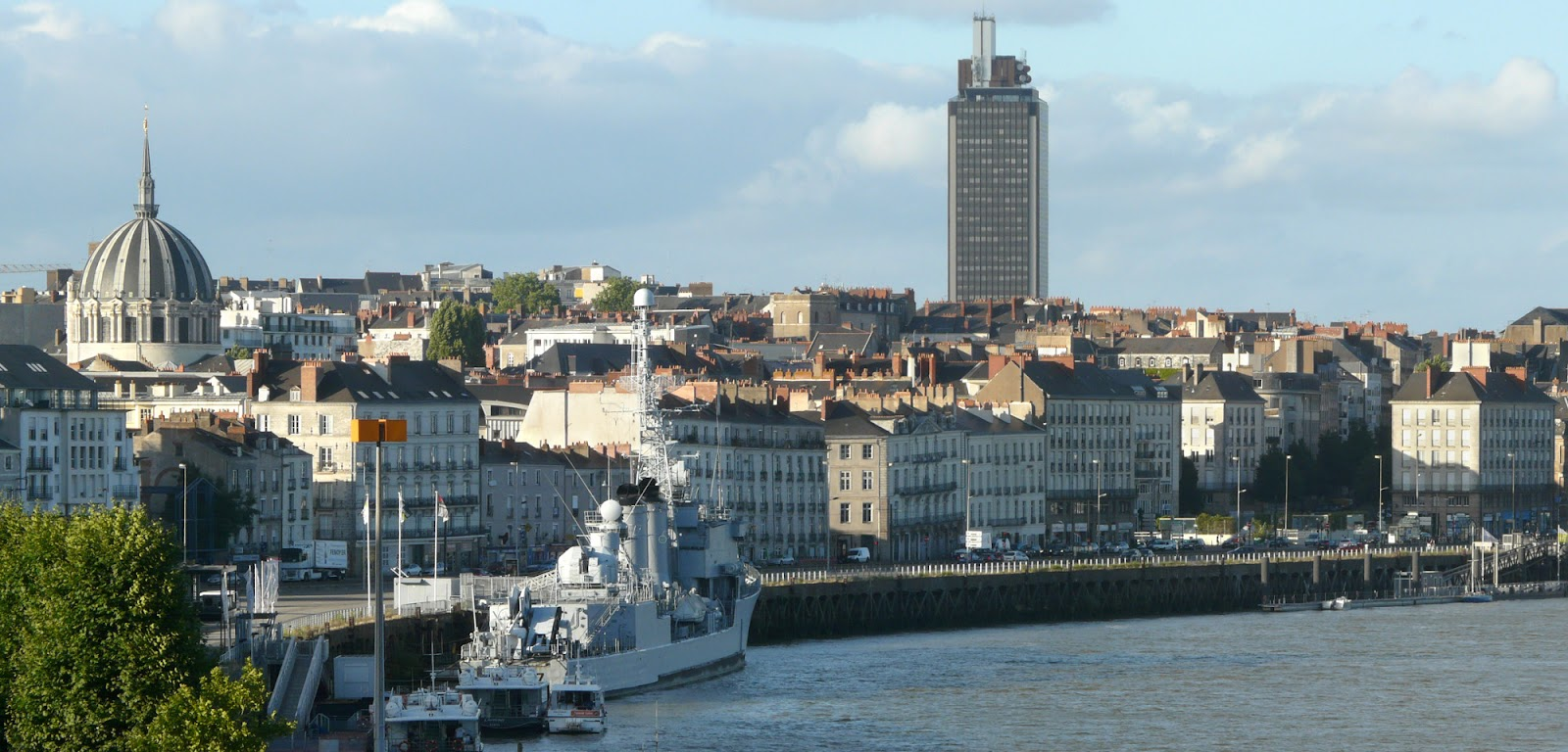 city view of nantes, france. river in foreground, parked military ship and traditional french buildings lining the coast. highrise building in background, on a sunny day in france.