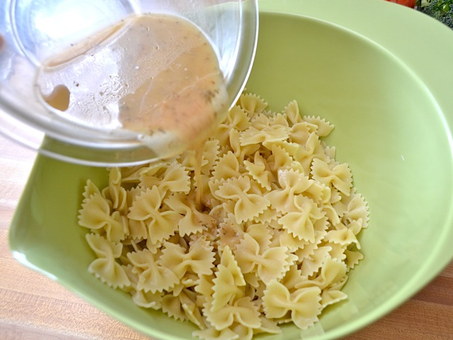 Cooked pasta and vinaigrette being added to large mixing bowl