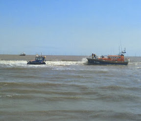 Lifeboat at sea being thrown a line from caterpillar submersible tractor