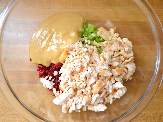 chopped chicken and dressing added to bowl with celery and cranberries