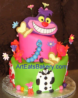 Alice in Wonderland two tier mad hatter custom birthday cake with the cheshire cat, butterflies, musrooms, flowers, catapiller, and cards