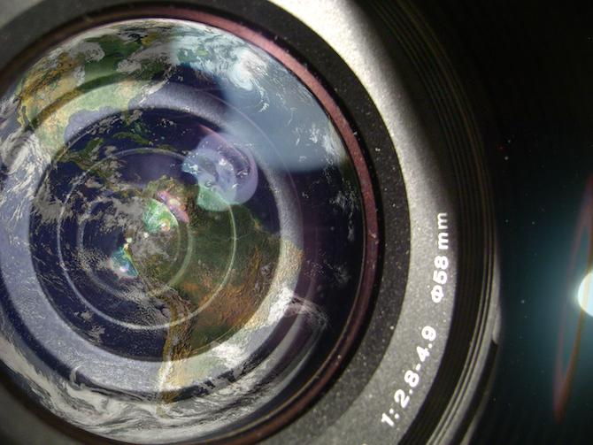 Montaje fotografico de la lente de un objetivo y el reflejo de la Tierra