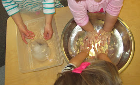 Children put their hands into warm water and hold ice as they learn about the properties of water.