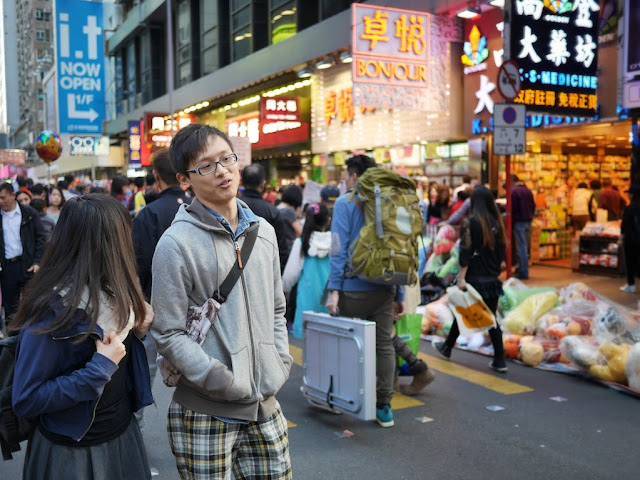 young man and woman talking to each other while walking on Sai Yeung Choi Street South