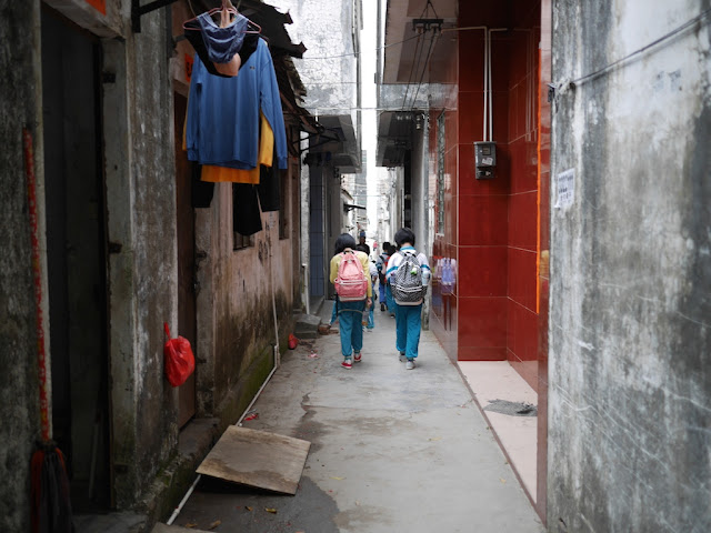 elementary school girls walking down a narrow pedestrian alley in Yangjiang, China