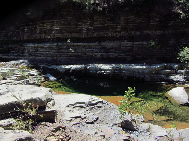 a cliff of layers stands as the backdrop to a narrow, deep pool