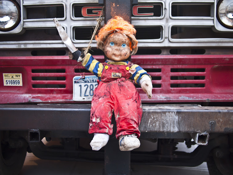 Photo of a doll strapped to the front grill of a construction truck in DUMBO