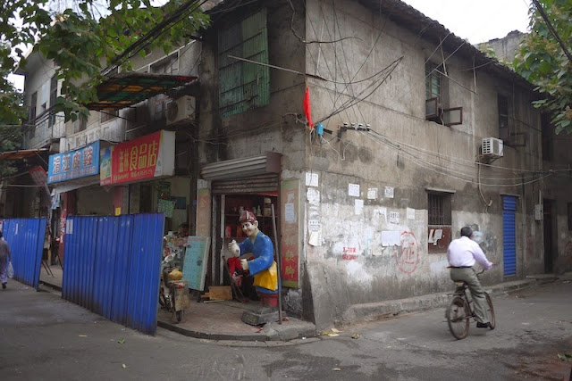 man riding a bike next to a building marked for demolition at Beizheng Street in Changsha, China