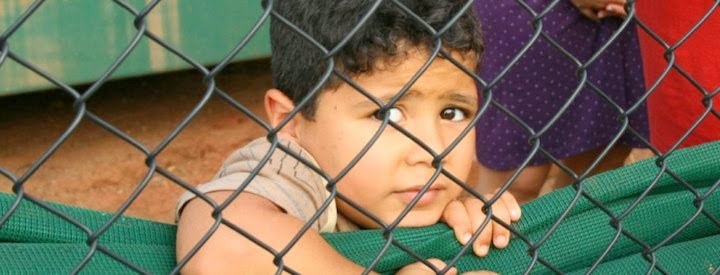 Child behind wire fence