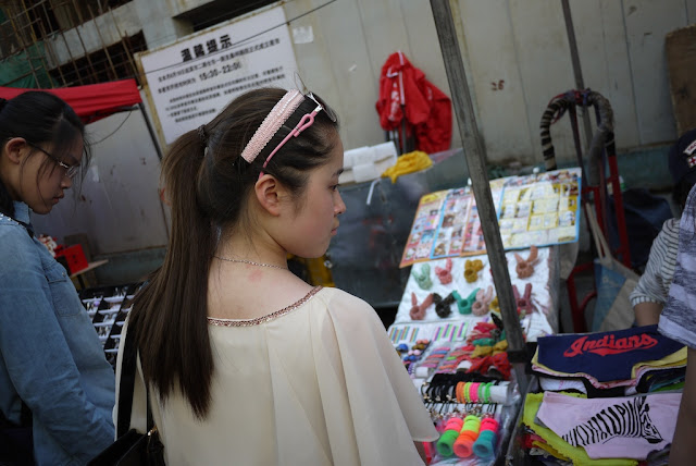 young woman look at items at a street market