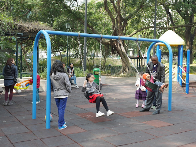 adults watching kids on a swing set at the King George V Memorial Park in Kowloon, Hong Kong