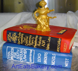 Lady Justice sugar figure on top of red and blue 3D law books custom 50th birthday cake for a lawyer