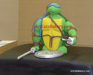 Teenage mutant Ninja turtle coming out of a manhole in the road custom fondant Groom's cake