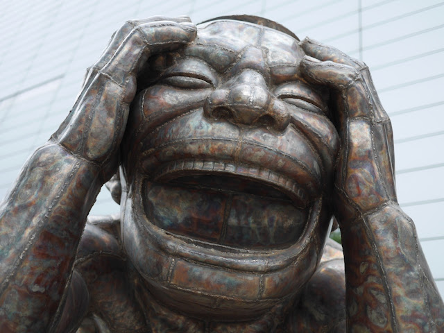 "the laughing head of one of Yue Minjun's steel sculptures named ""The Laugh that can be Laughed is not the Eternal Laugh"""