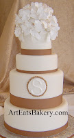 Four tier white fondant wedding cake with brown ribbons, monogram, edible pearls and sugar orcid flower topper idea picture