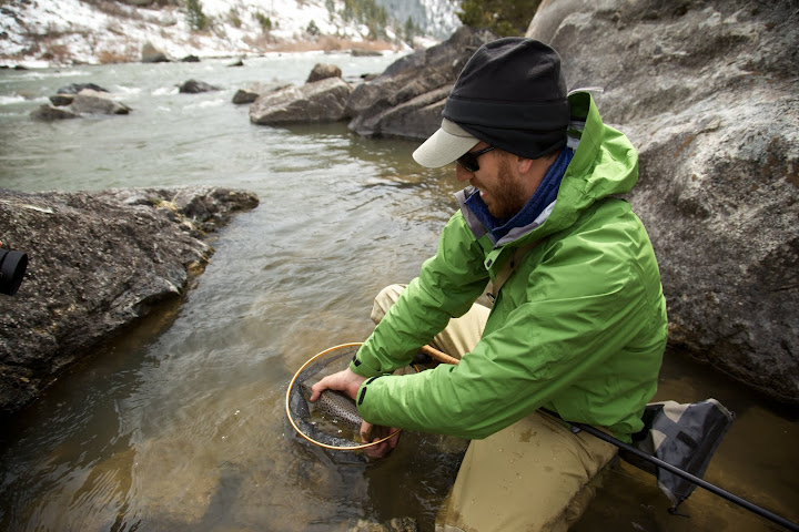 Holding a trout from the side with tenkara