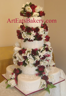 Traditional white fondant Four tier wedding cake with lace and royal icing piping separated by red and white silk flowers