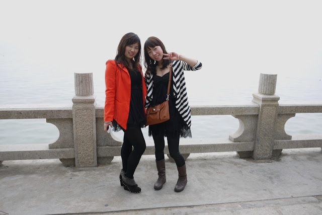 two young ladies posing in front of sea in Zhuhai