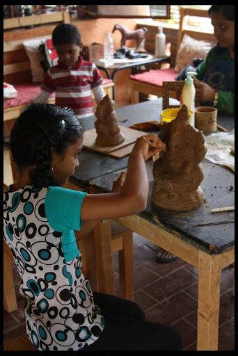 A kid giving the finishing to the clay Ganesh