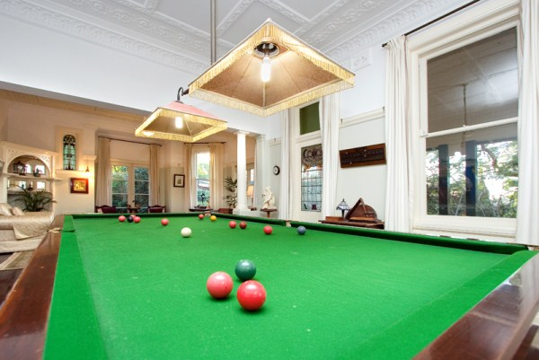 Games room with two 'eye' windows centre left, leadlight glass windows and plaster ceiling with Australian motifs