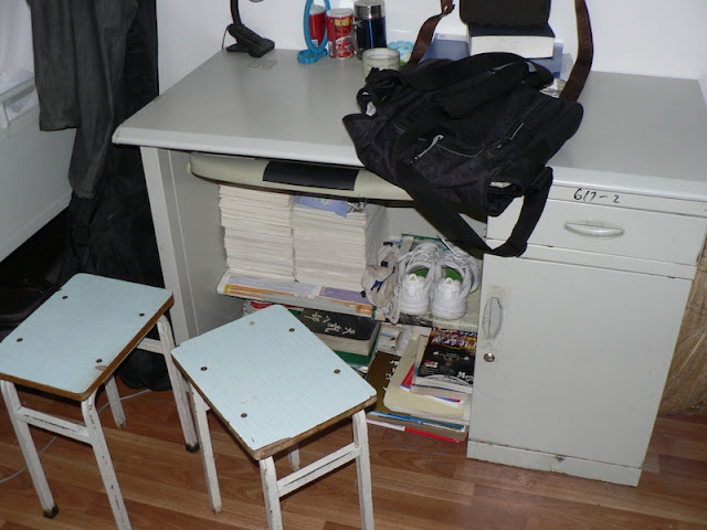 books stacked underneath a desk in a dorm room at Dalian Maritime University in China