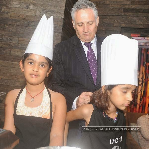 Antony helping a kid with her apron during the chocolate making session hosted Ritu Beri at the Delhi Baking Company, JW MArriott, Aerocity.