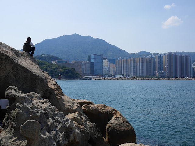 man sitting on a rock and looking across the water at Lei Yue Mun, Hong Kong