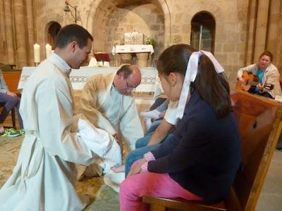 El párroco Jesús Montejano y el seminarista Moisés Tena lavan los pies a un conjunto de niños de nuestra parroquia