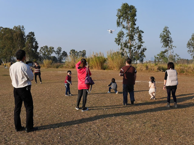 man operating a small quadcopter drone as adults and kids watch