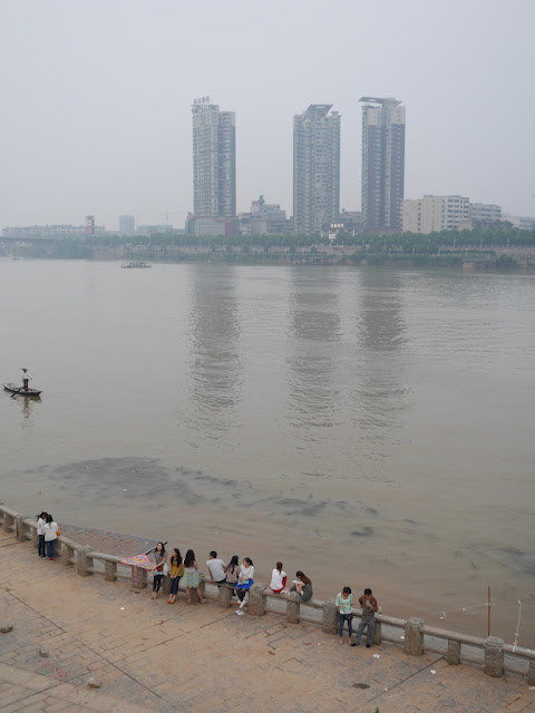 people one a stone railing next to the Xiang River in Hengyang