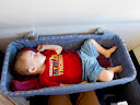 """This is on our flight to Kenya for a leadership meeting. Matimu's a bit too big for the """"basinets"""" provided for babies on flights, but he slept in it anyway. He doesn't mind tight spaces!"""
