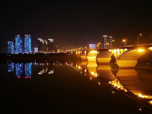 evening view of a bridge over Changsha's Xiang River with brightly lit buildings in the background