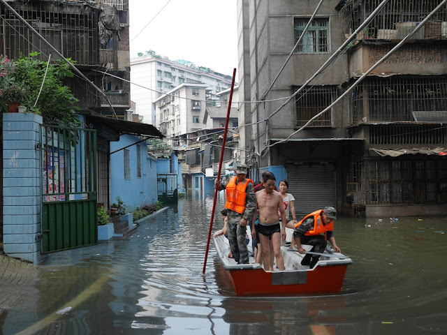 People's Liberation Army soldiers wearing urban camouflage uniforms navigating a boat with residents from a flooded neighborhood