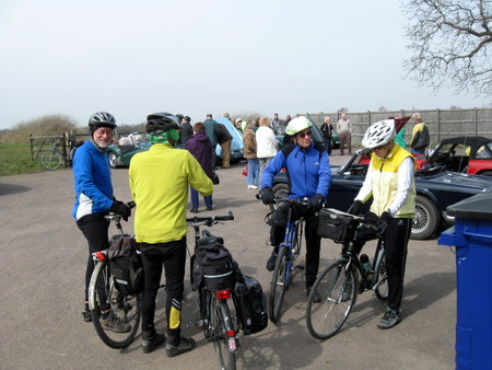 Group of cyclists in front of old cars