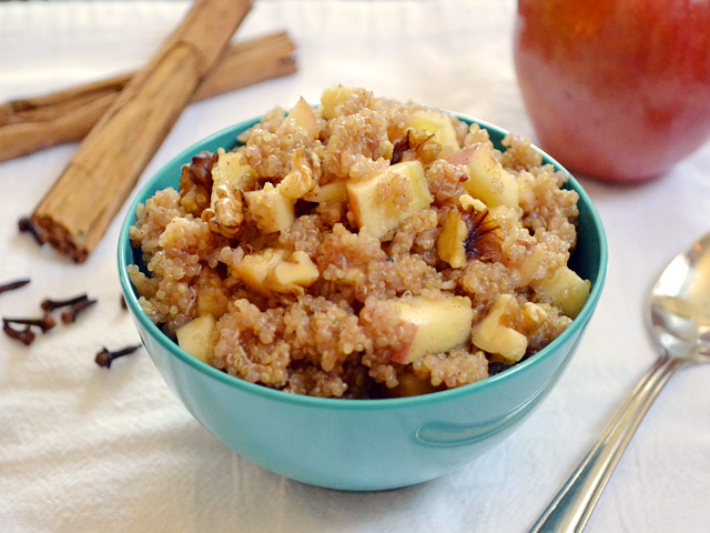 Bowl of Apple Nut Quinoa with a spoon and cinnamon sticks on the side