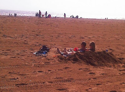 hot beach day with couple dug in sunbathing