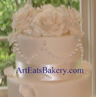 Three tier custom unique ivory fondant wedding cake with handmade sugar roses,petals, pearls, satin and lace ribbon closeup