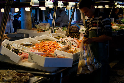 A vendor setting up a stall at the Fish Markets - Venice, Italy