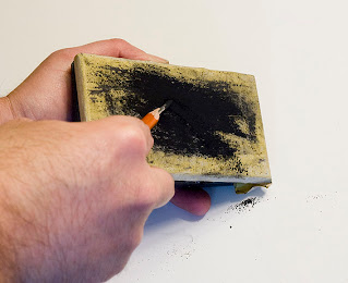 Use a sanding block to finish sharpening the charcoal pencil.